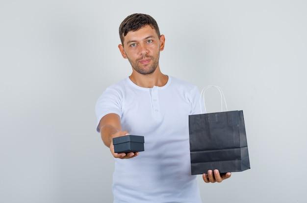 Junger mann, der geschenkbox und papiertüte im weißen t-shirt, vorderansicht hält.