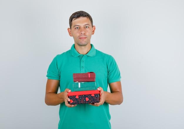 Junger mann, der geschenkboxen hält und im grünen t-shirt, vorderansicht lächelt.