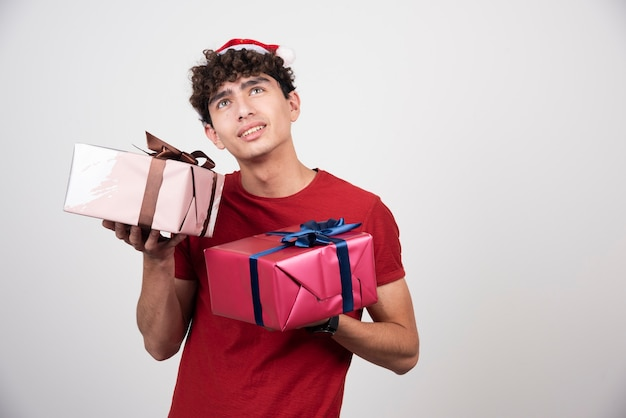 Junger mann, der geschenkboxen hält und oben seite schaut.