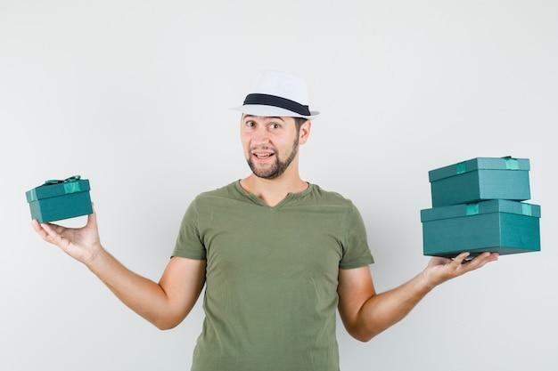 Junger mann, der geschenkboxen im grünen t-shirt und im hut hält und fröhlich schaut