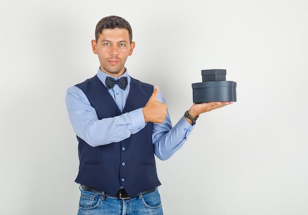 Junger mann, der geschenkboxen mit daumen oben im anzug hält