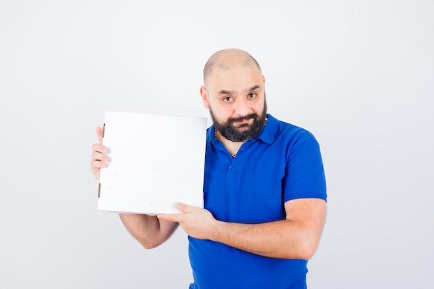 Junger mann, der geschlossene pizzaschachtel im t-shirt hält und glücklich schaut, vorderansicht.