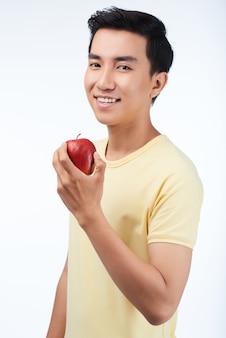Junger mann, der geschmackvollen apfel genießt