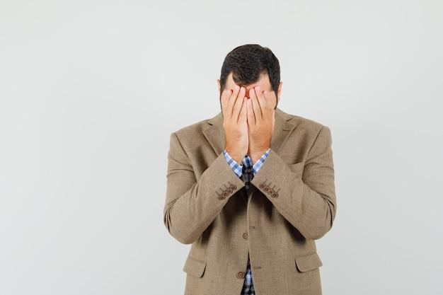 Junger mann, der gesicht mit händen im hemd, in der jacke bedeckt und traurig schaut. vorderansicht.