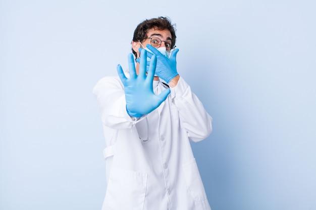 Junger mann, der gesicht mit hand bedeckt und andere hand nach vorne legt, um kamera zu stoppen. coronavirus-konzept