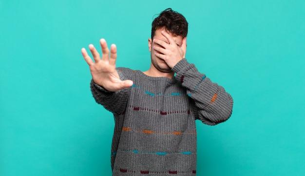 Junger mann, der gesicht mit hand bedeckt und andere hand nach vorne legt, um kamera zu stoppen, fotos oder bilder ablehnend