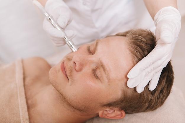 Junger mann, der gesichtsbehandlungsbehandlung durch kosmetikerin erhält