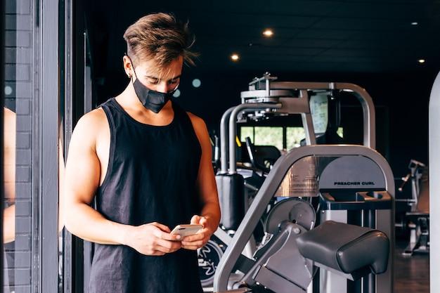 Junger mann, der gesichtsmaske trägt, schaut auf sein smartphone im fitnessstudio