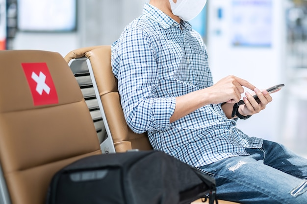 Junger mann, der gesichtsmaske trägt und mobiles smartphone im flughafen verwendet