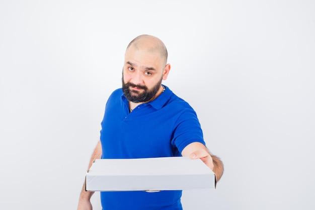 Junger mann, der geste im t-shirt zeigt und süß aussieht, vorderansicht.