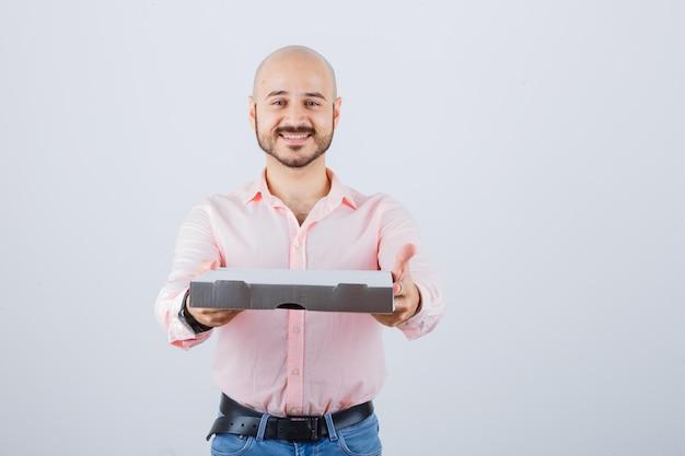 Junger mann, der geste in hemd, jeans zeigt und positiv aussieht, vorderansicht.