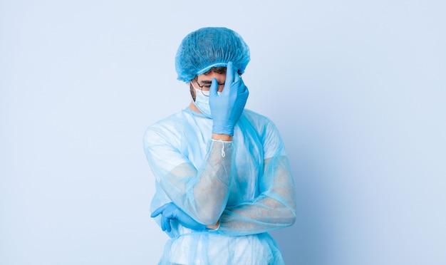 Junger mann, der gestresst, beschämt oder verärgert mit kopfschmerzen aussieht und gesicht mit hand bedeckt. coronavirus-konzept