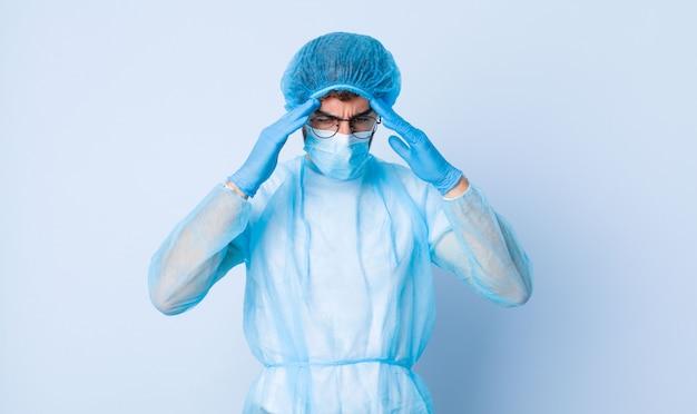 Junger mann, der gestresst und frustriert aussieht, unter druck mit kopfschmerzen arbeitet und mit problemen beunruhigt ist. coronavirus-konzept