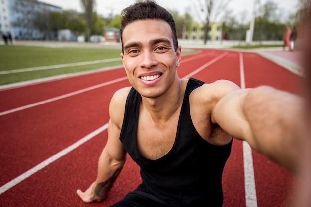 Junger mann der gesunden eignung, der auf der rennstrecke nimmt selfie am handy sitzt