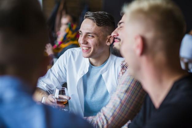 Junger mann, der getränke mit seinen freunden genießt