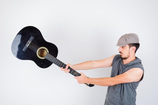 Junger mann, der gitarre in grauem t-shirt und mütze hält und gutaussehend aussieht