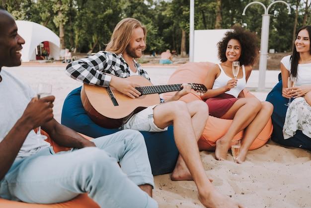 Junger mann, der gitarre spielt und für freunde singt