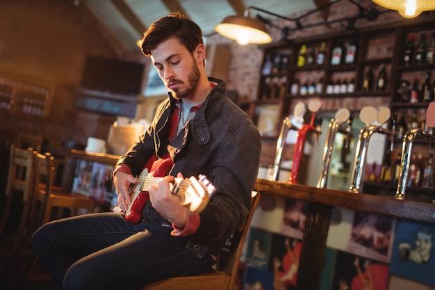 Junger mann, der gitarre spielt