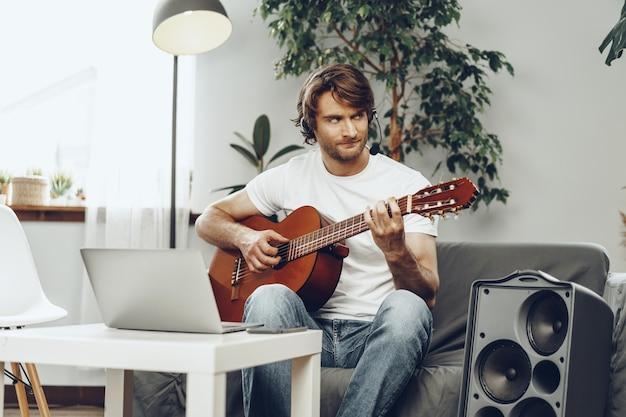 Junger mann, der gitarrentutorial auf seinem laptop beobachtet