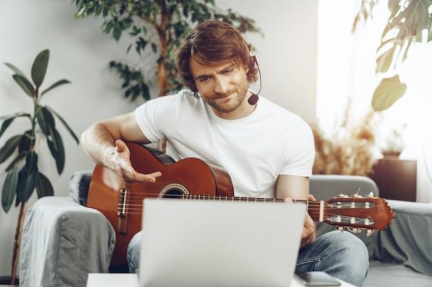 Junger mann, der gitarrentutorial auf seinem laptop zu hause beobachtet