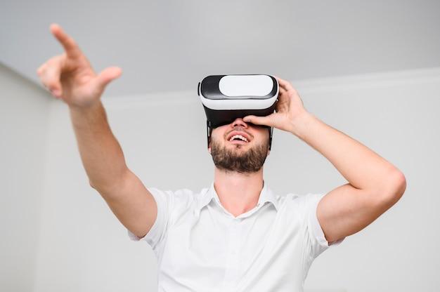Junger mann, der gläser der virtuellen realität verwendet