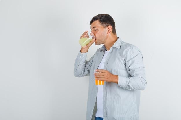 Junger mann, der glas saft im hemd trinkt
