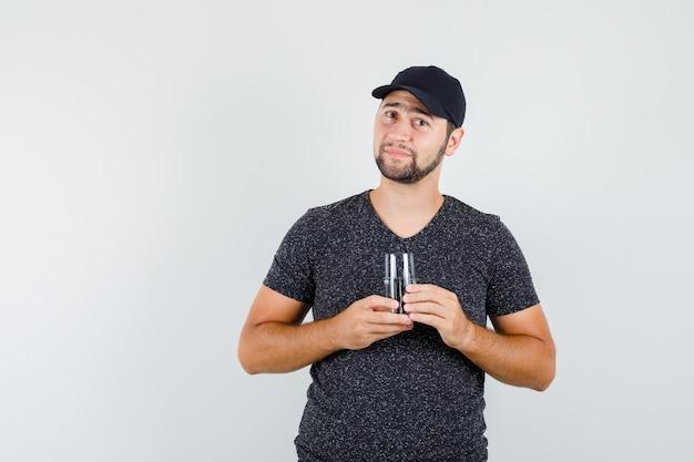Junger mann, der glas wasser im t-shirt und in der kappe hält und erfreut schaut