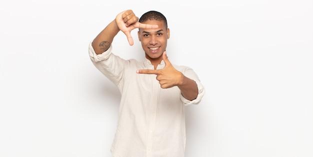 Junger mann, der glücklich, freundlich und positiv fühlt, lächelt und ein porträt oder fotorahmen mit händen macht