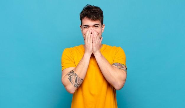 Junger mann, der glücklich, fröhlich, glücklich und überrascht aussieht, mund mit beiden händen bedeckend