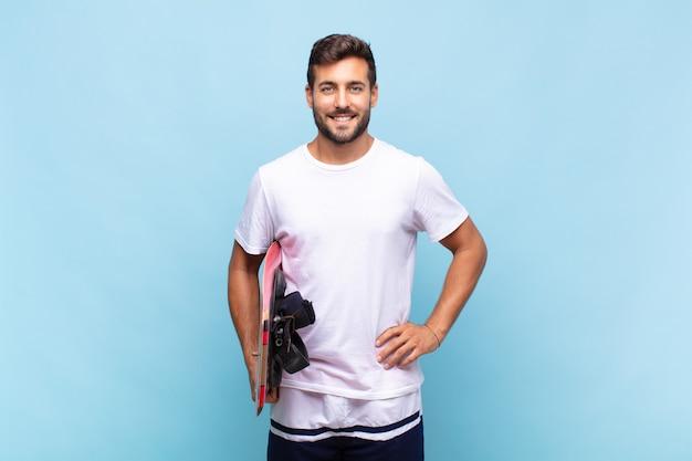 Junger mann, der glücklich mit einer hand auf hüfte lächelt und selbstbewusstes lächeln isoliert