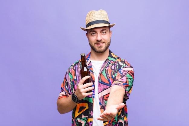 Junger mann, der glücklich mit freundlichem, selbstbewusstem, positivem blick lächelt und ein objekt oder konzept anbietet und zeigt Premium Fotos