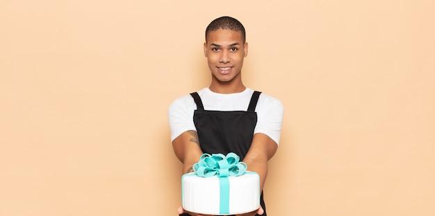 Junger mann, der glücklich mit freundlichem, selbstbewusstem, positivem blick lächelt und ein objekt oder konzept anbietet und zeigt