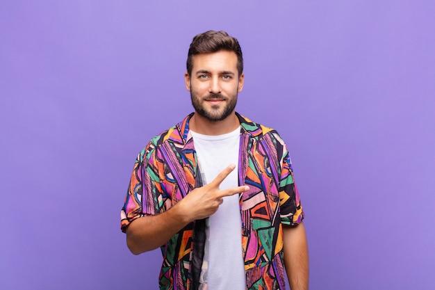 Junger mann, der glücklich, positiv und erfolgreich fühlt, mit der hand, die v-form über brust bildet, sieg oder frieden zeigend
