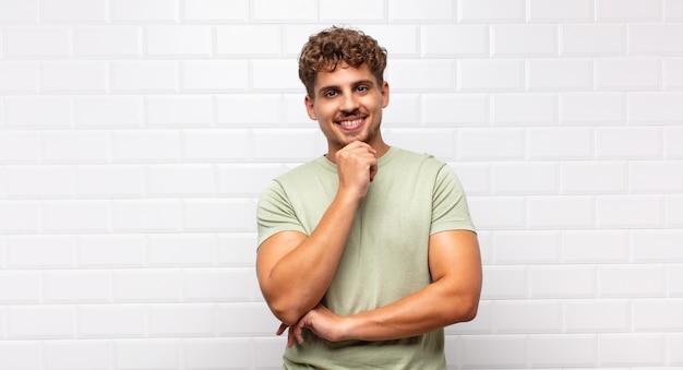 Junger mann, der glücklich schaut und mit der hand am kinn lächelt, sich wundert oder eine frage stellt, optionen vergleicht
