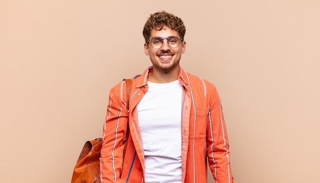 Junger mann, der glücklich und doof mit einem breiten, lustigen, verrückten lächeln und weit geöffneten augen aussieht. studentenkonzept
