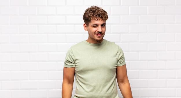 Junger mann, der glücklich und freundlich schaut, lächelt und ihnen mit einer positiven einstellung ein auge zuzwinkert