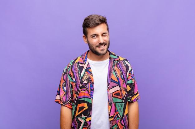 Junger mann, der glücklich und freundlich schaut, lächelt und ihnen mit einer positiven einstellung ein auge zwinkert Premium Fotos