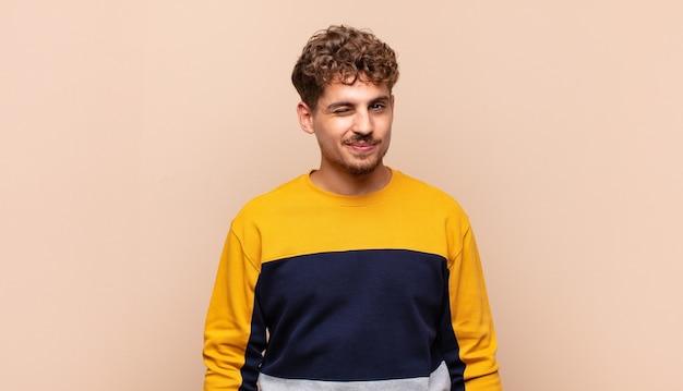 Junger mann, der glücklich und freundlich schaut, lächelt und ihnen mit einer positiven einstellung ein auge zwinkert