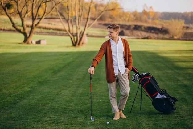 Junger mann, der golf spielt