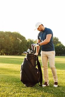 Junger mann, der golfschläger hält