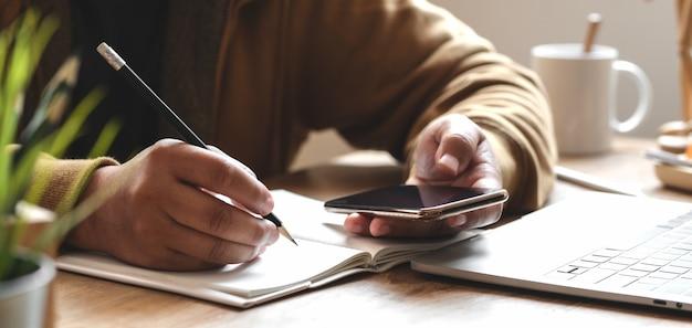 Junger mann der großaufnahme, der an seinem projekt mit smartphone im bequemen büro arbeitet