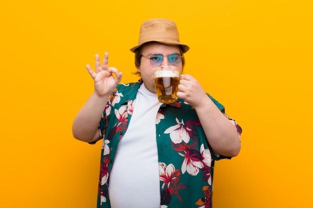 Junger mann der großen größe mit einem halben liter bier gegen flache wand