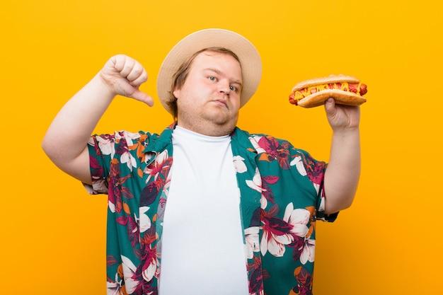 Junger mann der großen größe mit einem hotdog gegen flache wand