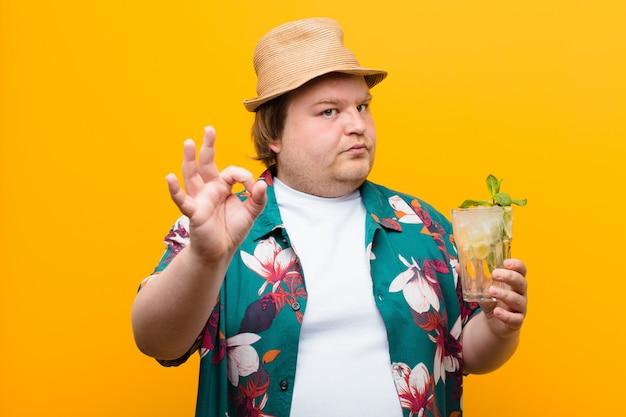 Junger mann der großen größe mit einem mojito getränk gegen flache wand