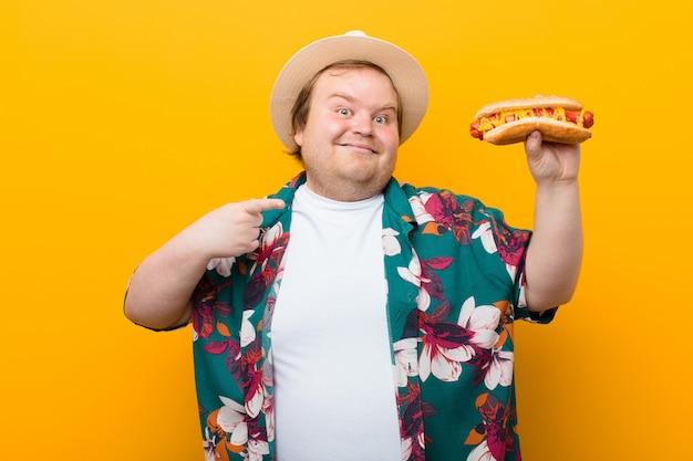 Junger mann der großen größe mit einer flachen wand des hotdogs