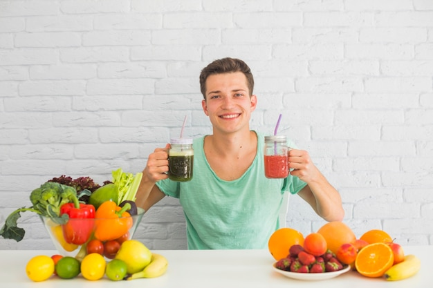 Junger mann, der grünen und roten smoothie in seiner hand mit gesundem lebensmittel auf tabelle hält