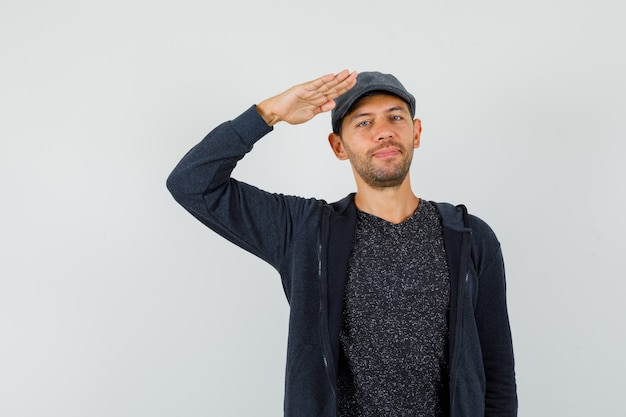 Junger mann, der grußgeste in t-shirt, jacke, mütze zeigt und selbstbewusst aussieht.