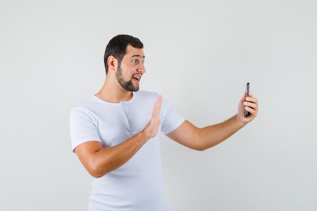 Junger mann, der grußgeste zeigt, während videoanruf im weißen t-shirt macht und glücklich schaut.