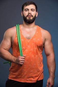 Junger mann, der gummi für sport auf dunkelblauer wand hält.