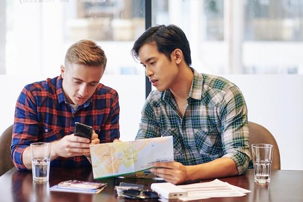 Junger mann, der gutes hotel zeigt, das er in der buchung der mobilen anwendung zu freund mit papierkarte in händen fand